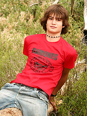 Naked long-haired boy posing outdoor